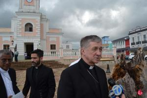 Cardenal Cupich es entrevistado por varios medios tanto locales, como de Chicago. Al fondo, la Catedral de Fajardo.